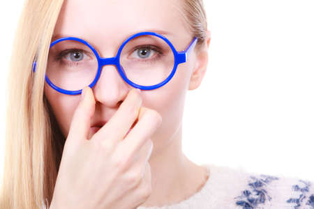 smells: Stinky smells, clogged concept. Nerdy woman in big funny glasses holding nose smelling bad scent