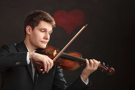 Music passion, hobby concept. Romantic young man man dressed elegantly playing on wooden violin. Studio shot on dark background with red heart