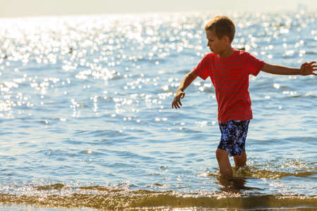 Water fun and joy outside. Little boy walking through the sea ocean. Lonely kid playing outdoors in summer clothes. Stock Photo