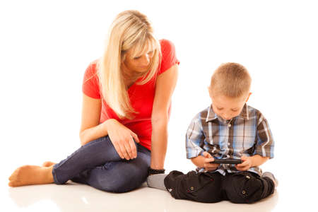 Family, children, parenthood, technology and internet concept. Mother and son playing video game on smartphone isolated on white photo