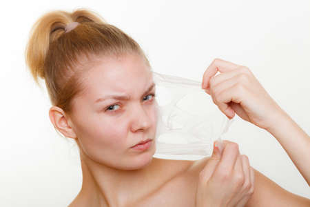Beauty skin care cosmetics and health concept. Young woman face, girl removing facial peel off mask. Peeling. Фото со стока
