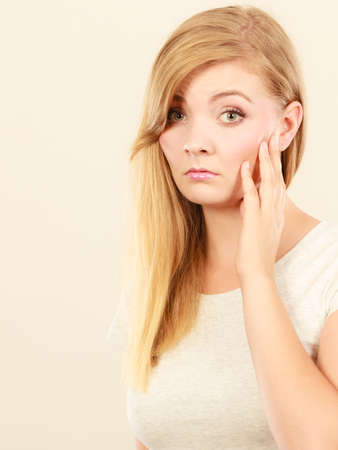 Face expression, emotions concept. Sad cute young blonde attractive woman in white t shirt feeling toothache