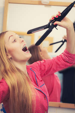 Haircare and hairstyling concept. Woman having fun while straightening her long blond hair using straightener tool. Stock Photo