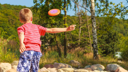 Play and fun concept. Little playful enjoyable boy kid throwing frisbee disc. Male child having fun playing outdoor on beach. photo