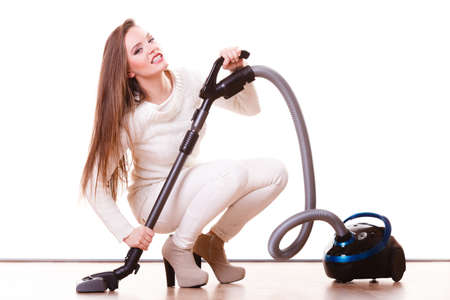 Woman vacuuming the house. Funny girl with vacuum cleaner. Housework Stock Photo