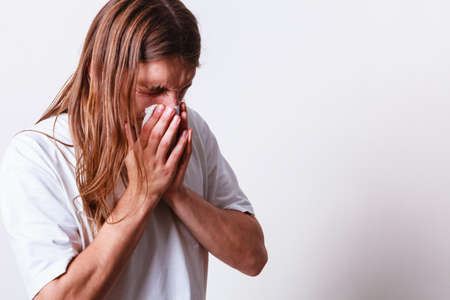 alergenos: Alergias y concepto de frío. El hombre de pelo largo joven enferma con el tejido higiénico. Hombre sonarse la nariz.