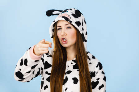 Teen girl in funny nightclothes, pajamas cartoon style showing angry face expression pointing, wagging finger, studio shot on blue. Negative emotion concept.