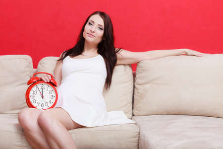 tummy time: Pregnancy, motherhood, expecting concept. Pregnant woman holding big red old fashioned clock, waiting for childbirth