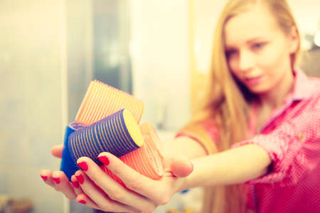 hair roller: Styling at home concept. Happy woman holding hair rollers in bathroom about to make fancy coiffure