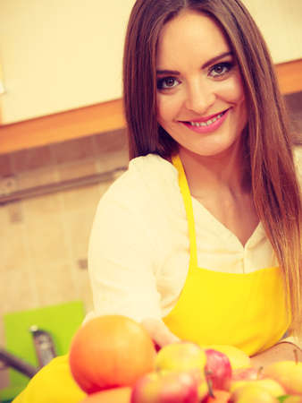 Apples hobby diet salad concept. Female cook working in kitchen. Young lady in apron preparing healthy food out of natural fruits. Stock Photo