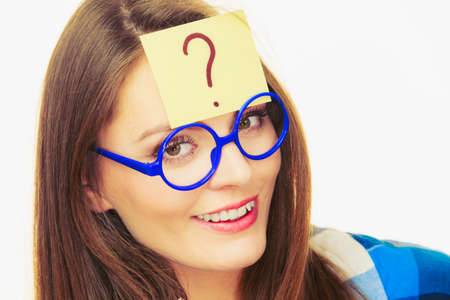 Woman confused thinking seeks a solution, paper card with question mark on her head. Doubtful young female in glasses studio shot on white Stock Photo