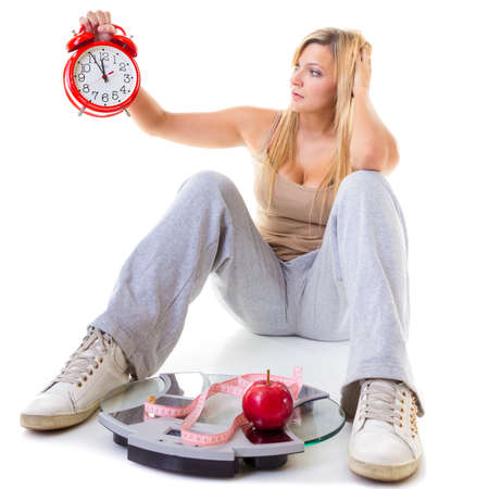 Diet, fitness, slimming, loosing weight concept. Curvy, worried woman holding big old fashioned clock sitting on weighing machine
