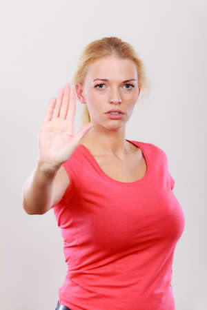 banned: Refusal, denial signs. Blonde woman showing stop gesture with open hand, refusing something. Stock Photo