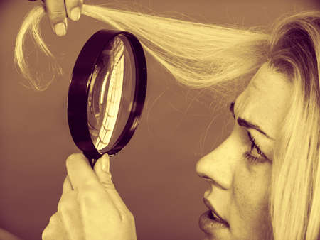 appearance: Haircare, health problem concept. Unhappy woman looking at ends of her blonde hair through magnifying glass. Sepia Stock Photo