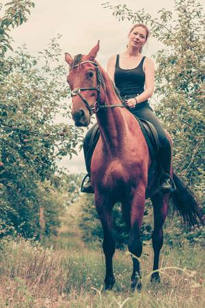 Animal, concept équitation. Jeune femme assise et de débarrasser sur un cheval par le jardin le jour de printemps ensoleillé Banque d'images - 79836708