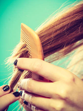 haircutting: Haircare concept. Female hand combing brown hair with wooden comb on blue green