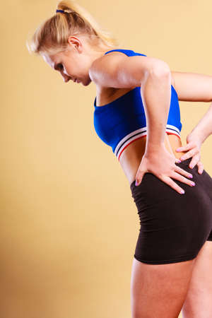 Sport training gym and health problem. Young fit female with backache. Woman suffering from back pain
