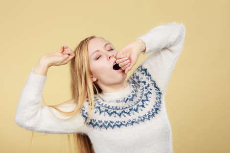 Tiredness, too much work at school concept. Sleepy yawning blonde teenage woman in jumper feeling exhausted