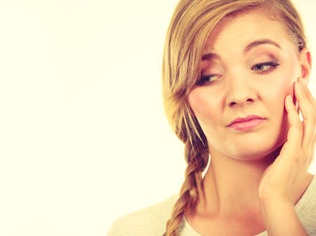 Face expression, adolescence problems concept. Teenage girl in blonde braid hair making bored face.