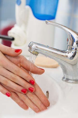 lavarse las manos: Woman cleaning washing hands under flowing tap water in the bathroom. Female hands with red nails manicure. Hygiene, skin treatment concept. Foto de archivo