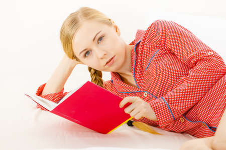 Girl lying in bed reading book. Young blonde female wearing red dotted pajamas relaxing at home on mattress. Stock Photo