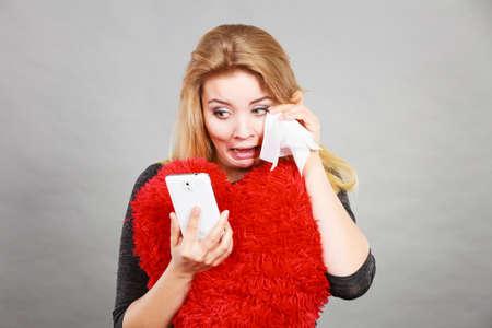 sobbing: Betrayal, bad relationship, hurt love concept. Sad heartbroken woman crying and looking at her phone. Stock Photo