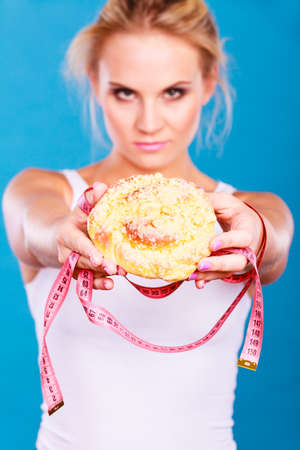 Unhealthy nutrition overweight concept. Fit female saying no to sweet dessert. Woman dietician holding sweet bun recommending non sugar diet on blue Stock Photo