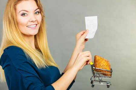 shopper: Happy woman holding shopping basket with bread looking at bill receipt, enjoying low prices.