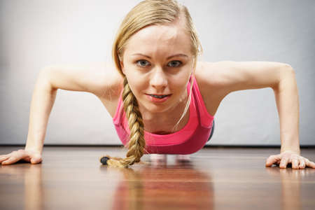 Woman training, working out at home doing push ups, being fit and healthy. Close up shot