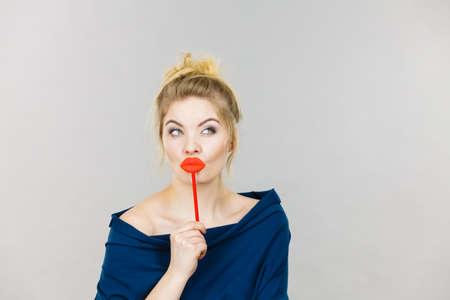 막대기에 큰 빨간 입술을 들고 재미 있은 여자. 금발의 젊은 여성이 회색 배경에 파티에 대 한 준비. 유머 의상, 스마트 및 카니발 개념입니다.