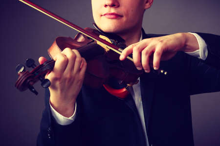 Music passion, hobby concept. Close up young man man dressed elegantly playing on wooden violin. Studio shot on dark background Stock Photo