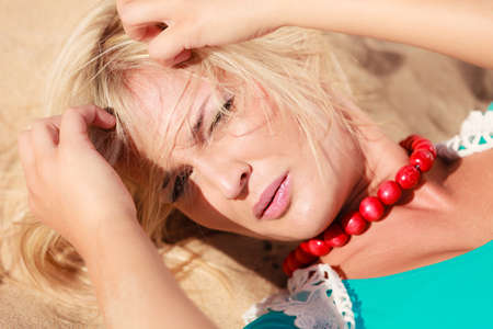 Holidays relax time concept. Blonde woman lying on sand. Lady has big necklace. Female is chilling on the beach. Reklamní fotografie
