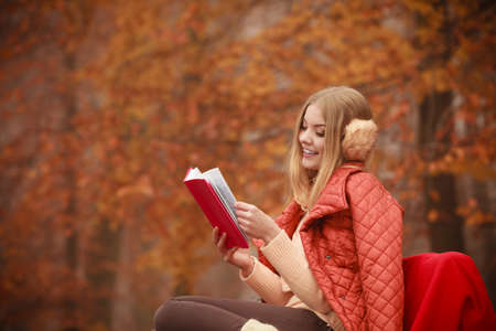 Outdoor nature season relax leisure concept. Young lady with literature. Blonde girl reading red book sitting on bench in autumnal woodland.