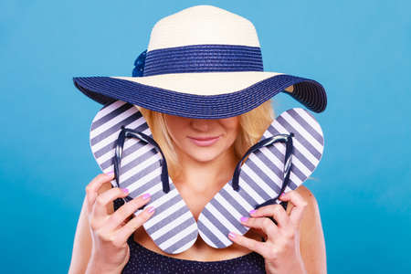 Summer trendy fashionable outfit ideas concept. Blonde unrecognizable mysterious woman wearing blue dress and sun hat holding flip flops. Stock Photo