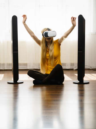 Young woman wearing virtual reality goggles vr box with arms outstretched sitting on floor in living room, listening to music. Connection, technology, new generation and progress concept.