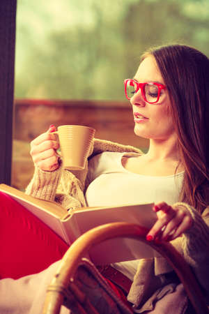 rocker girl: Calm and coziness. Young woman at home sitting comfortable on rocking chair in front of window relaxing in her living room reading book holds coffee mug