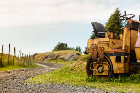 Agriculture, harvesting, gardening machinery concept. Combine harvester standing next to coutryside path on sunny day Stock Photo