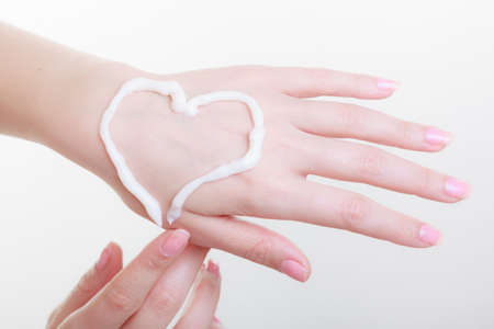 moisturize: Beauty, cosmetics, concept. Cream on woman hand, heart shape. Studio shot on white background