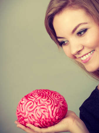 considering: Intellectual expressions, being focused concept. Closeup of attractive woman smiling face expression holding brain