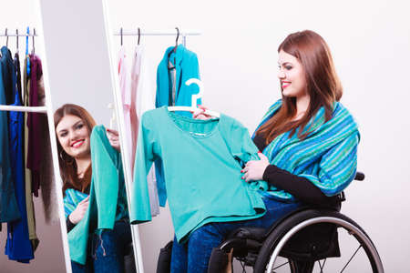 Real people, disability and handicap concept. Teen girl handicapped woman sitting on wheelchair choosing clothes in wardrobe or looking for some clothes in shop