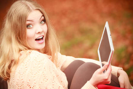 Young blonde girl in park. Cheerful lady sitting on bench browsing her tablet surrounded by autumnal vegetation. Stock Photo