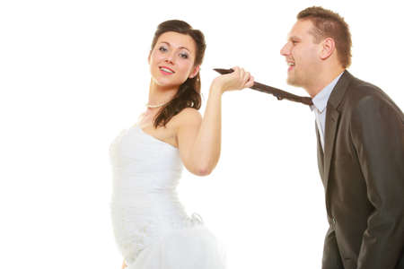 Relationship command concept. Dominant bride wearing wedding dress pulling groom tie, isolated.