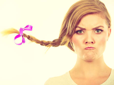 Face expression, adolescence problems concept. Teenage girl in blonde braid windblown hair making angry faces. Stock Photo