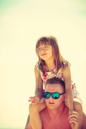 sunburnt: Father wearing sunglasses and swimming suit giving daughter piggyback on sunny day Stock Photo