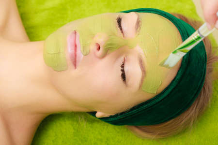 Someone applying woman green algae mud mask on face. Beauty, relaxation, skincare, wellness in spa concept.