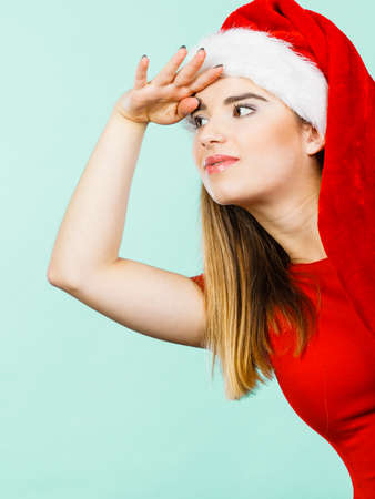 hand on forehead: Xmas, seasonal clothing, winter christmas concept. Young woman wearing Santa Claus helper costume looking at something with hand on forehead Stock Photo