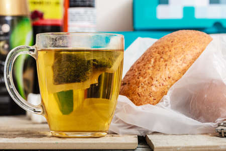 Meals in unusual surroundings concept. Glass with tea and bread in messy interior