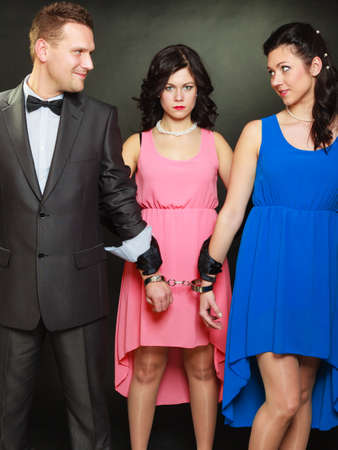 Couple cheating problems, love triangle concept. Wife and husband in handcuffs, jealous woman standing behind them photo
