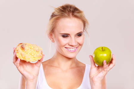 suspicion: Woman holds in hand cake sweet bun and apple fruit choosing, trying to resist temptation, make the right dietary choice. Weight loss diet dilemma gluttony concept.