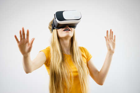 Young woman wearing virtual reality goggles headset, vr box, stretching arms. Connection, technology, new generation and progress concept. Studio shot on gray